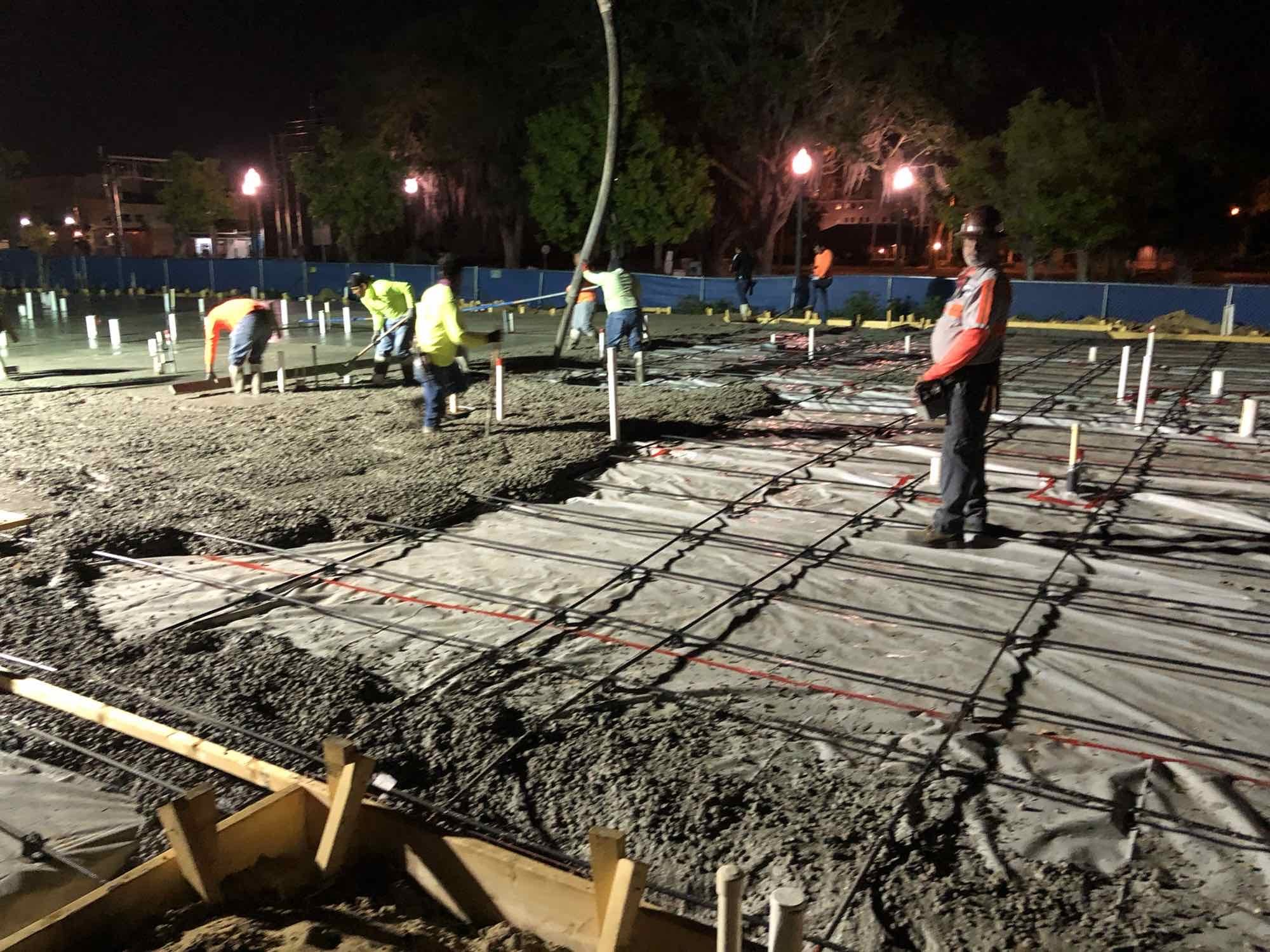 Toho Construction at night, showing workers laying concrete.