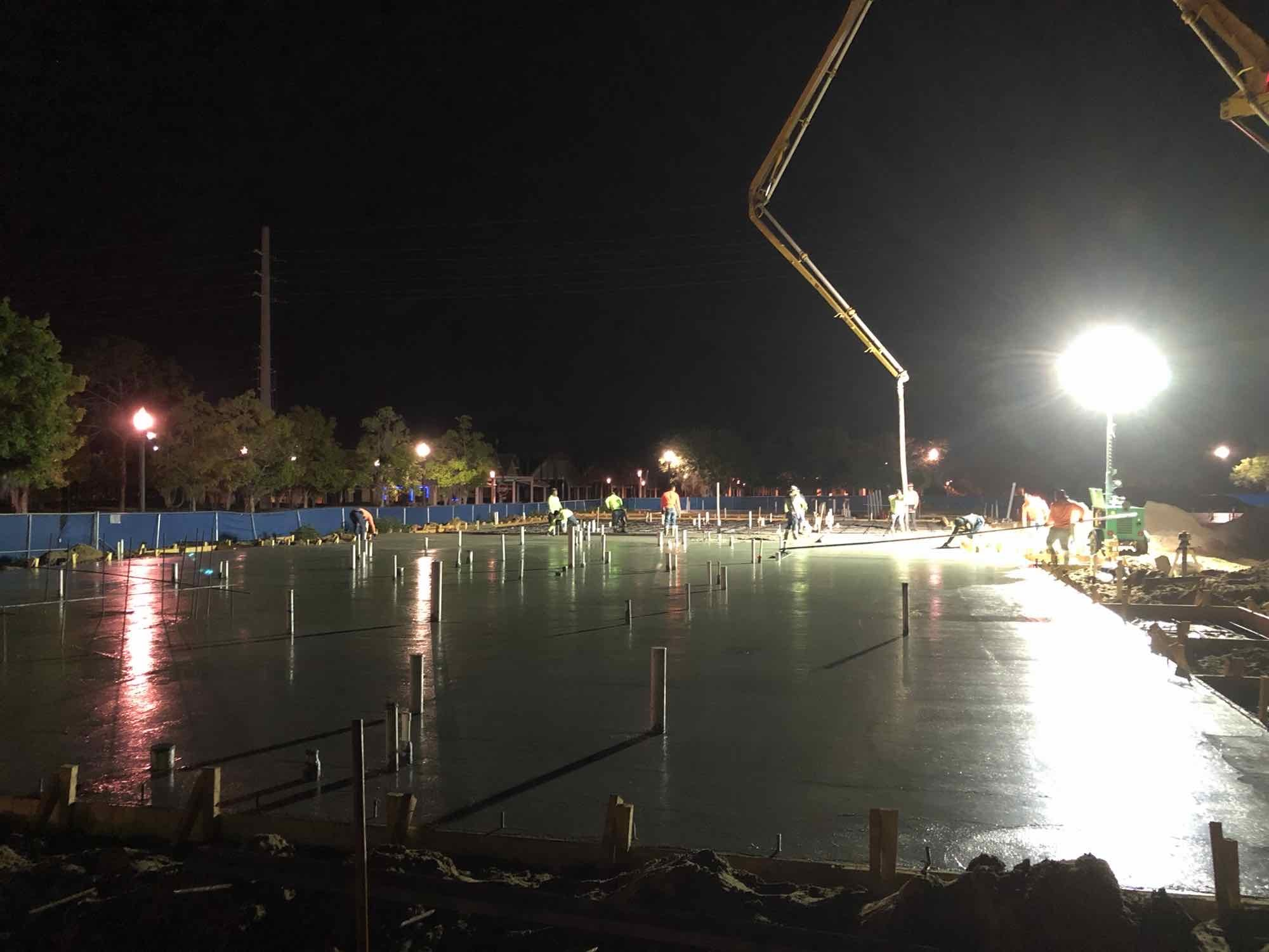 Concrete being poured by overhead crane.